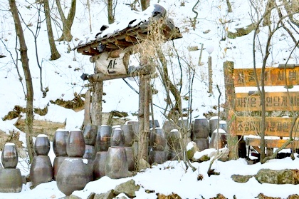 Stacked kimchi jars in a snowy valley next to a sign in Korean
