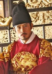 Masquerade - Lee Byung Hun dressed in a royal red robe and seated on a gilded throne;