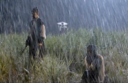 Ha Ji Won is crouched in the foreground, holding her arm as heavy rain pours down on her. Lee Seo Jin stands nearby, not looking at her, and in the background, a woman with a hat like a parasol stands watching the scene