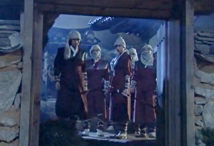 Boss Jang and several of his comrades stand, dressed in fighting clothes ans masking scarves, framed by the gateway in a stone wall;