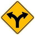 Road sign for a fork in the road ahead - one arrow splits into two