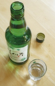 An uncapped bottle of soju with a full shot glass beside it