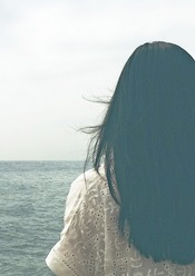 A photo from the back of a woman with long black hair looking out over the sea on a cloudy day